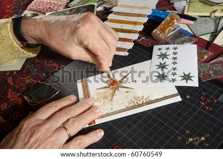 Hands of a woman crafting and scrap-booking christmas cards - stock photo