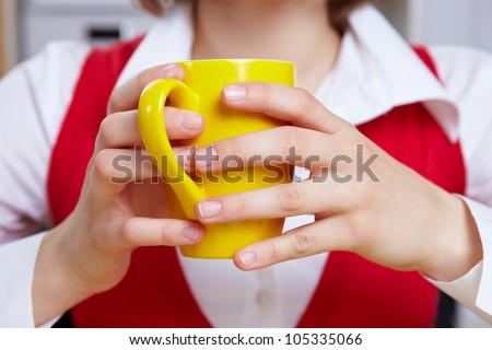 Hands of a woman holding yellow cup of coffee in office