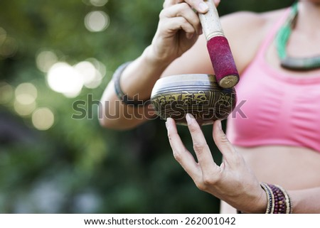 Hands of a woman playing tibetan singing bowl in nature - stock photo