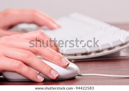 Hands of a woman using mouse and keyboard - stock photo