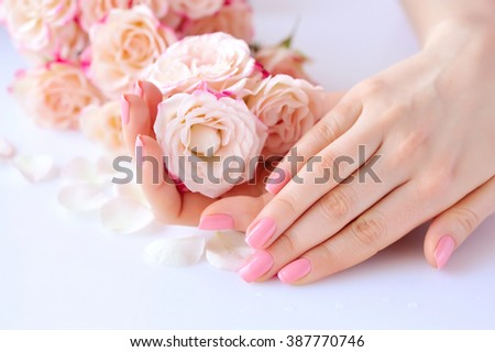 Hands of a woman with pink manicure on nails  and roses against white background - stock photo