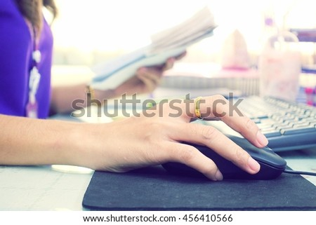 Hands of a woman working at the office using the mouse. - stock photo