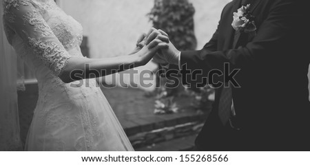 hands of a young newly wed couple, black and white - stock photo