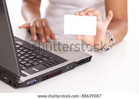 Hands of a young woman holding a blank gift card in front of the laptop computer - stock photo
