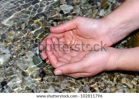 hands of a young woman refreshing in the fresh and pure water of a mountain stream