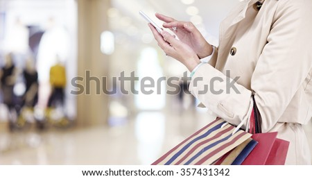 hands of a young woman using mobile phone in modern shopping mall. - stock photo