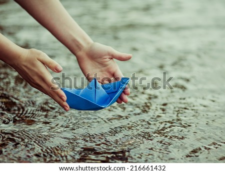 hands of a young woman with a paper boat by the lake in summertime (focus on the beat) - stock photo
