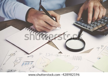 Hands of accountant business man with calculator and pen - stock photo