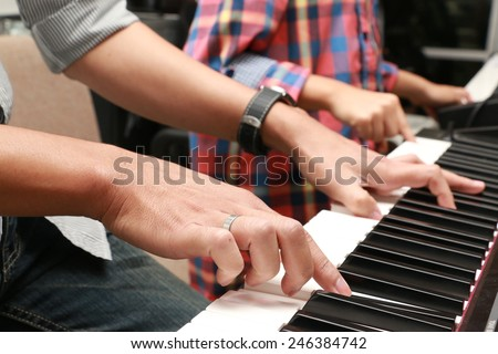 Hands of adult and child on piano keyboard - stock photo