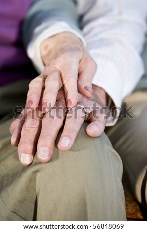Hands of affectionate elderly couple touching on knee