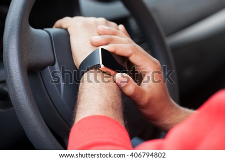 Hands of African male model using his modern smart wrist watch sitting in a car. This new internet technology lets this person always stay connected to internet and social media. - stock photo
