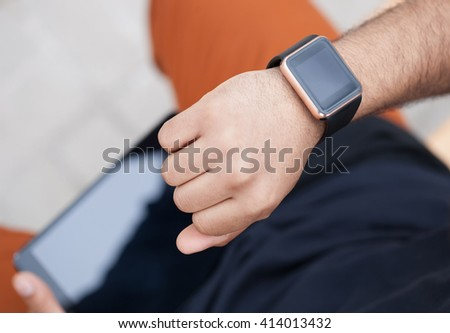 Hands of African man looking at his trendy smart watches working on black tablet pc. Modern gadgets that lets you always stay connected to internet,social media.Macro close up on wrist watches. - stock photo