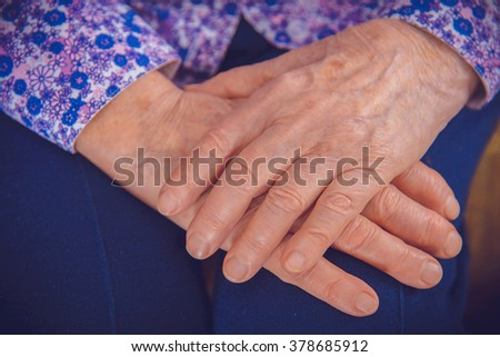 Hands of an elderly grandmother - stock photo