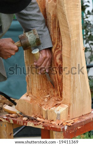 Hands of an elderly man, carving a wood sculpture with a chisel and mallet. - stock photo