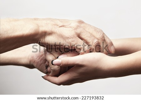 Hands of an elderly man holding the hand of a younger woman - stock photo
