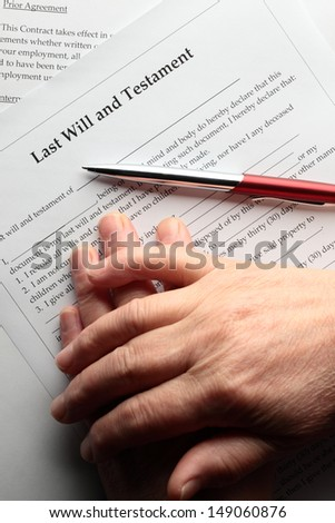 Hands of an elderly person waiting to sign a last will document.