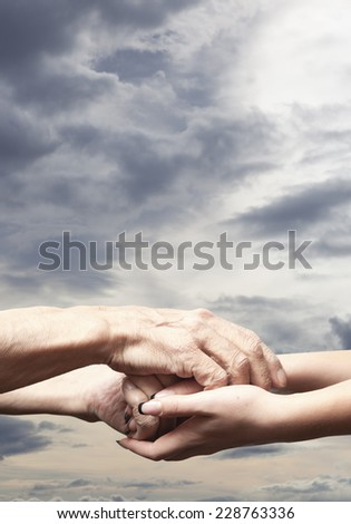 Hands of an elderly senior holding the hand of a younger woman - stock photo