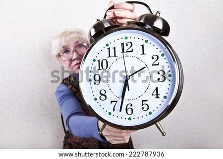 Hands of an elderly woman holding a clock. Time goes on. - stock photo