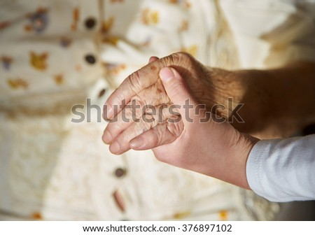 Hands of an elderly woman holding the hand of a younger woman. Lots of texture and character in the old ladies hands in clinic.