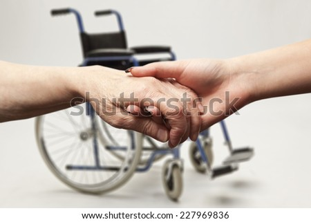 Hands of an elderly woman holding the hand of a younger woman on wheelchair background - stock photo