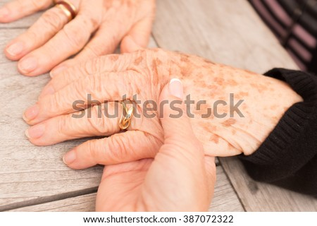 Hands of an elderly woman with freckles holding the hand of a younger woman.  - stock photo