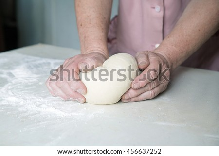 hands of an elderly woman with freckles knead the dough on the table with flour - stock photo