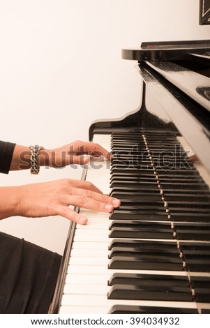 Hands of an elegant classical musician woman playing on piano. - stock photo