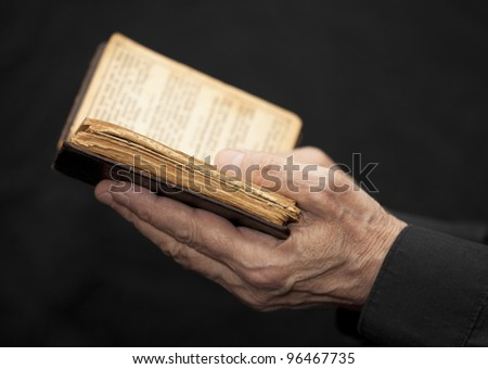 Hands of an old man holding a book - stock photo