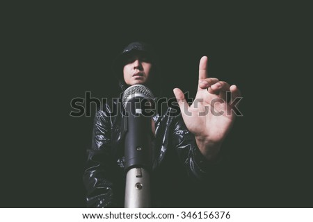 hands of asian handsome singer in black leather coat with dynamic microphone. isolated on black + art filter