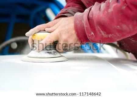 Hands of auto mechanic applying basic layer of polish - stock photo