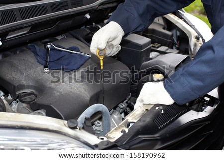 Hands of auto mechanic oil checking. Car repair service. - stock photo
