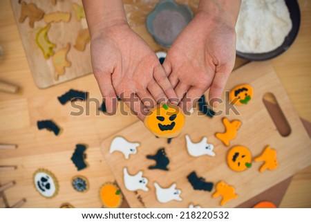 Hands of baker holding homemade pumpkin cookie - stock photo