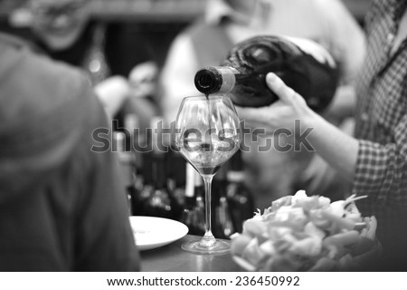 Hands of bartender pouring wine into a glass goblet, monochrome - stock photo