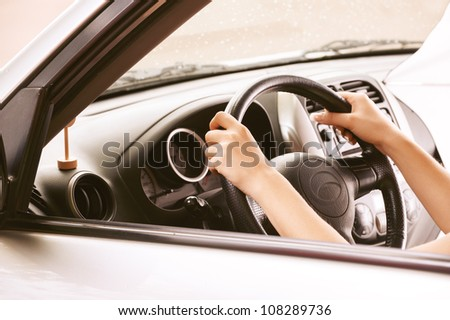 Hands of beautiful young woman in car.