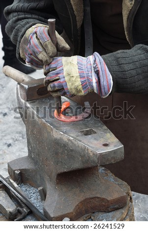 Hands of blacksmith making horseshoe
