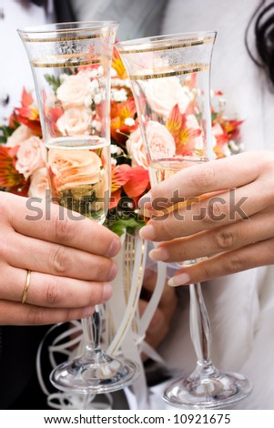 Hands of bride and groom holding two glasses of champagne. Low DOF, focus on hands - stock photo