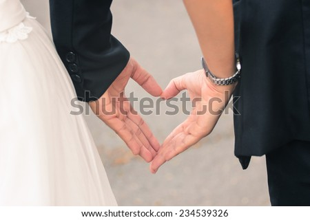hands of bride and groom in a shape of heart - stock photo