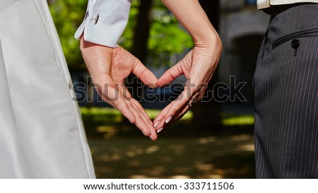 hands of bride and groom in a shape of heart