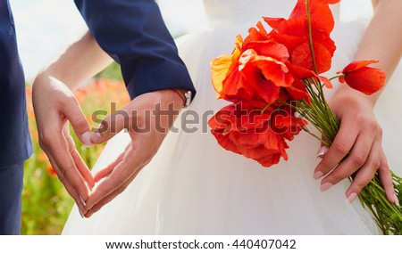Hands of bride and groom in a shape of heart. Wedding ,love,heartconcept. In the hands of the bride bouquet of poppies. Wedding couple in the poppy field.
