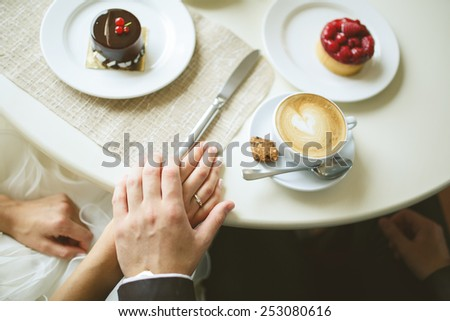 hands of bride and groom on table with cakes and cup of cappuccino - stock photo