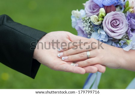 hands of bride and groom with rings and bouquet - stock photo