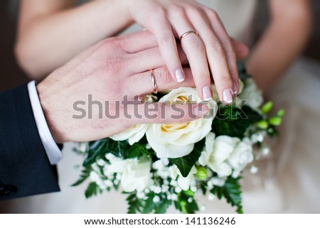 Hands of bride and groom with rings on bouquet