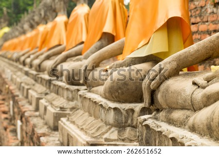 Hands of Buddha statues in a row (focused on the nearest) - stock photo