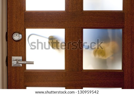 Hands of Burglar, thief  with gloves, holding crowbar trying to break in home, unlock door, blurred visible silhouette behind milky windows, with copy space. - stock photo