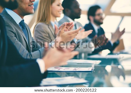 Hands of business partners applauding to reporter after listening to presentation at seminar, blurry - stock photo
