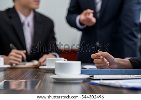 Hands of business person taking notes during meeting on office