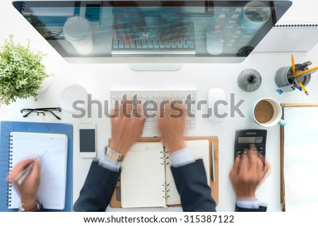 Hands of business person working at his table, blurred motion - stock photo
