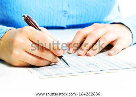 Hands of business woman filling tax form.