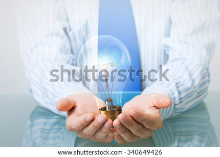 Hands of businessman holding with care glass light bulb - stock photo
