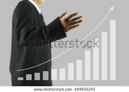Hands of businessman in black suit drawing a growing graph